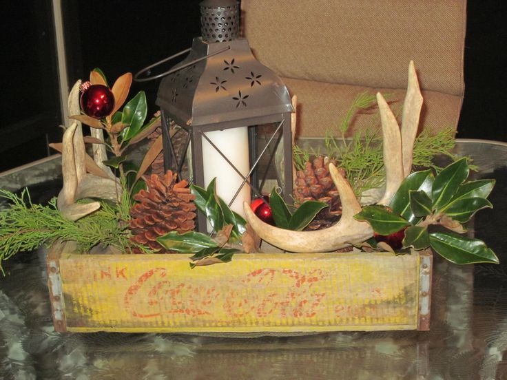 Centerpiece with cypress and magnolia cuttings, antler sheds, pincones and lantern