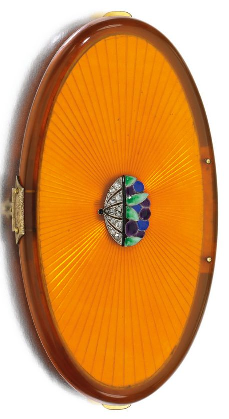 Enamel and diamond vanity case, 1920s. The oval blonde celluloid case applied with an enamel and rose diamond foliate motif, opening to reveal mirror and two compartments for powder and lipstick, measuring approximately 95 x 50 x 13mm, French assay and maker's marks, lipstick signed Bulgari. #ArtDeco #VanityCase #Bulgari