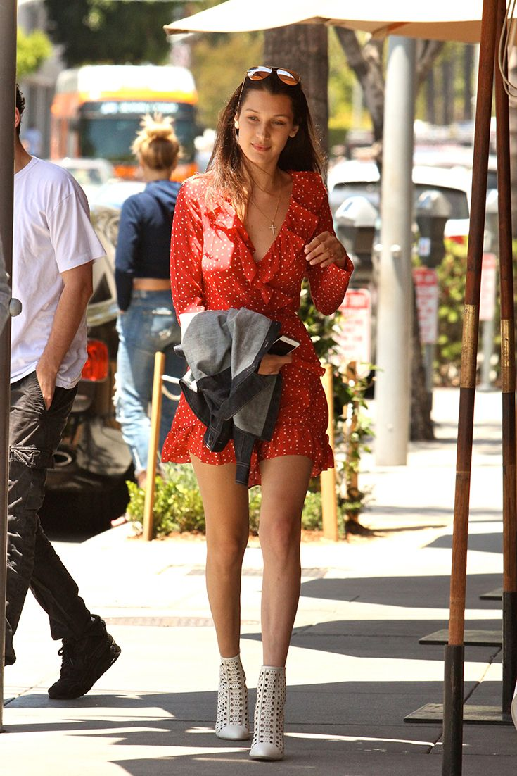 Bella Hadid smashing summer dressing in a red polka dot dress, mirrored aviators and white lazer-cut boots. Dang