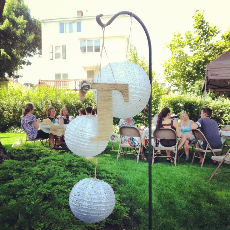 Twine wrapped monogram letter with eyelet paper lanterns. Use a shepards hook to hang. Vintage tea party bridal shower