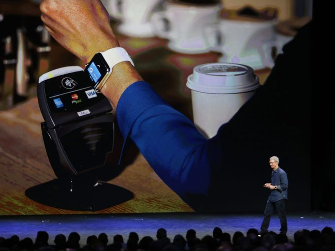 Tim Cook demonstrates the Apple Pay system using an Apple Watch  during Apple's launch event in Cupertino, Calif.