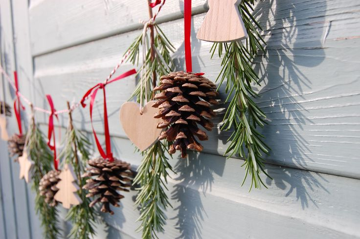 Christmas pine cone garland with fresh Rosemary sprigs and wooden cut out shapes