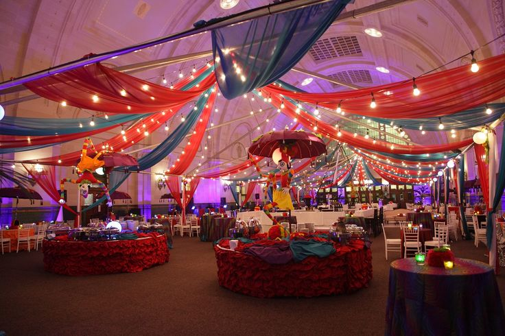 Lights and sheer draping create an elegant indoor carnival ...