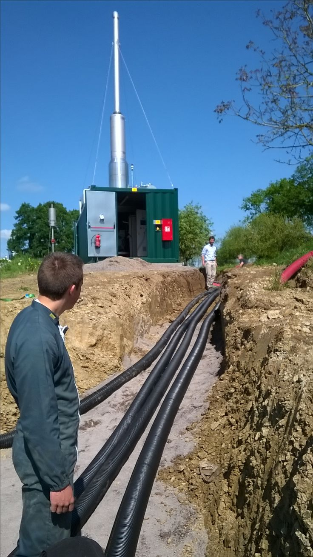 Opération de déroulage des couronnes de tuyaux pré-isolés Flexalen à la ferme du Moulin Guérin pour connecter l'unité de production de chaleur à partir de biogaz aux bâtiments.