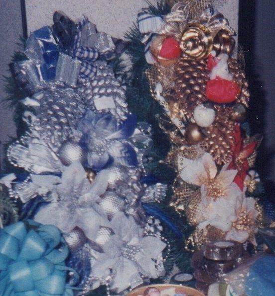 Enfeites natalinos para portas, janelas ou paredes com base em isopor esculpido formato oval (azul e prata), ou formato árvore de Natal (vermelho, branco e ouro), totalmente cheio de elementos natalinos: pinhas naturais, flores bico de papagaio, sinos, laços, bolas brilhantes e foscas, mini papai noel no enfeite vermelho e ouro, fios de contas de metal e spray prata no enfeite oval azul e prata, e fios de contas ouro e spray ouro no enfeite ouro e vermelho. Elo7 - MImos da Zelia.