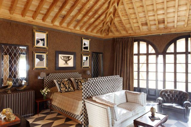 This very traditional Spanish room features a wood ceiling and patterned floor designed with two types of marbles. Bed upholstered in cut velvet by Colony; Sofá upholstered in Loro Piana cashmere; Two paintings by Castillo's brother painter Santiago Castillo.   - Veranda.com