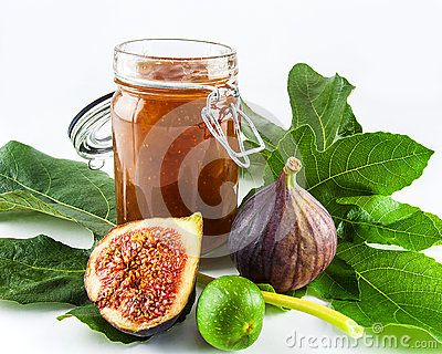 A close up of an open jar of fig jam with fruit and leaves