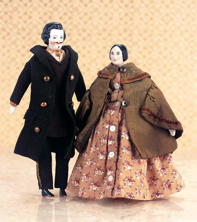 "Theriault's Antique Doll Auctions - Two Early German Porcelain Dollhouse Dolls - 7"" & 8"". Each has porcelain shoulder head with painted facial features and sculpted hair. A handsome gentleman has very full curly hair, moustache and goatee. Original blue felt flannel suit over muslin body with porcelain limbs. The woman has black sculpted hair drawn into a simple chignon, wearing layered antique costume over a wooden body with porcelain lower limbs. Germany - circa 1860."
