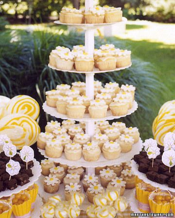 Daisy Shower Cupcake Centerpiece - The refreshments double as the decor in this baby shower centerpiece. Arrange color-coordinated cupcakes, candies, and miniature baskets or paper cups full of snacks on tiered platters and cake stands of different heights.