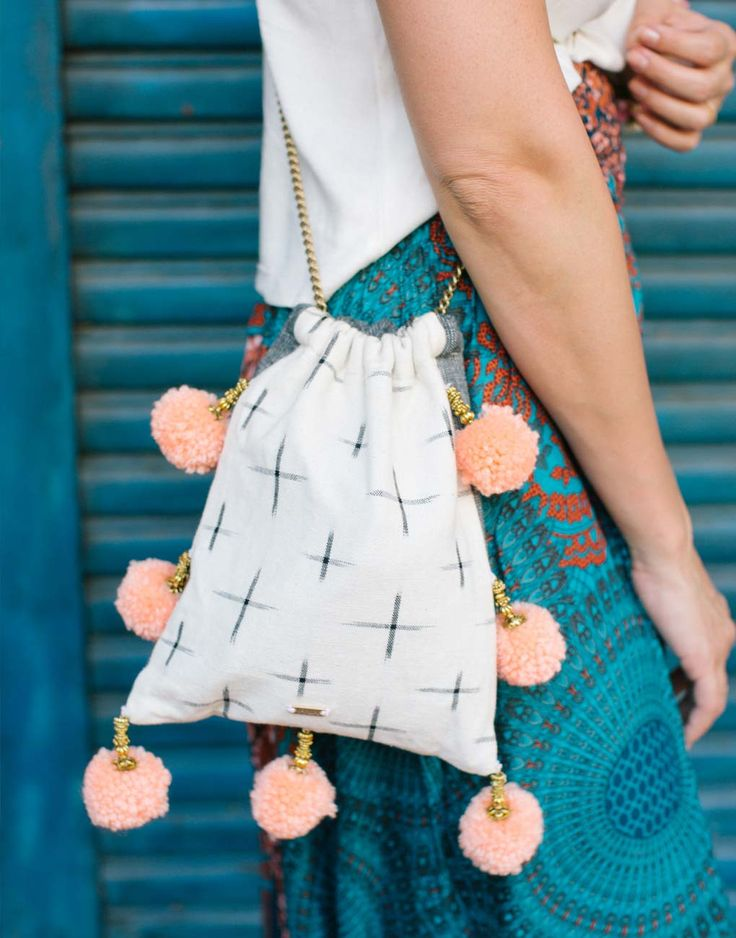 """- Description - Artisan We love this vibrant pom pom bag, perfect for the beach, brunch, and everything in between! * Approximately 9"""" long x 8"""" wide; 20"""" chain; 1.5"""" pom poms * As with all handwoven More"""