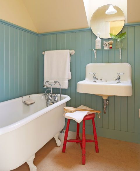 Extra-tall beadboard—painted in Benjamin Moore's Mill Springs Blue—covers the walls of this New Hampshire home's bathroom. The owner acquired the sink from a local gas station when they threw the fixture away; the claw-foot tub is a cast-off from a former landscaping client.