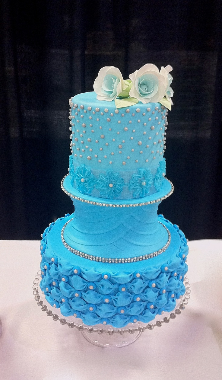La Quinceanera - I made this cake for a competition. My inspiration was the floral ribbon on the top tier that I purchased at Hobby Lobby. I loved the color of the ribbon so much that I decided to make a cake that looked like a dress. Quinceanera dresses are always made in such beautiful, vibrant colors. All tiers are made of fondant. The buttons are made of royal icing with an edible pearl attached to each one. The roses are gum paste. The ruffles are individual rectangles cut from fondant…