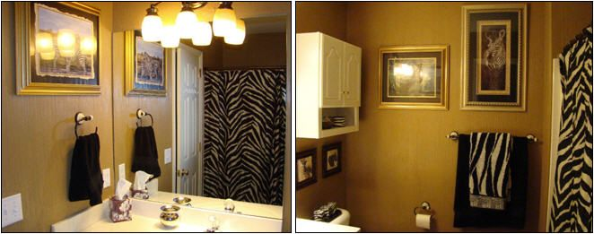 A safari inspired bathroom, with artwork depicting African wildlife, zebra-patterned towels,  shower curtain and candles, and textured walls resembling thatch.