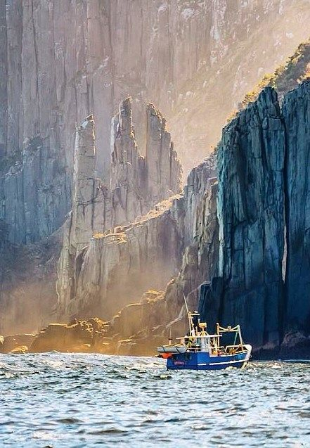 Fishing boat is dwarfed by the monster dolerite cliffs off the Tasman Peninsula, Tasmania