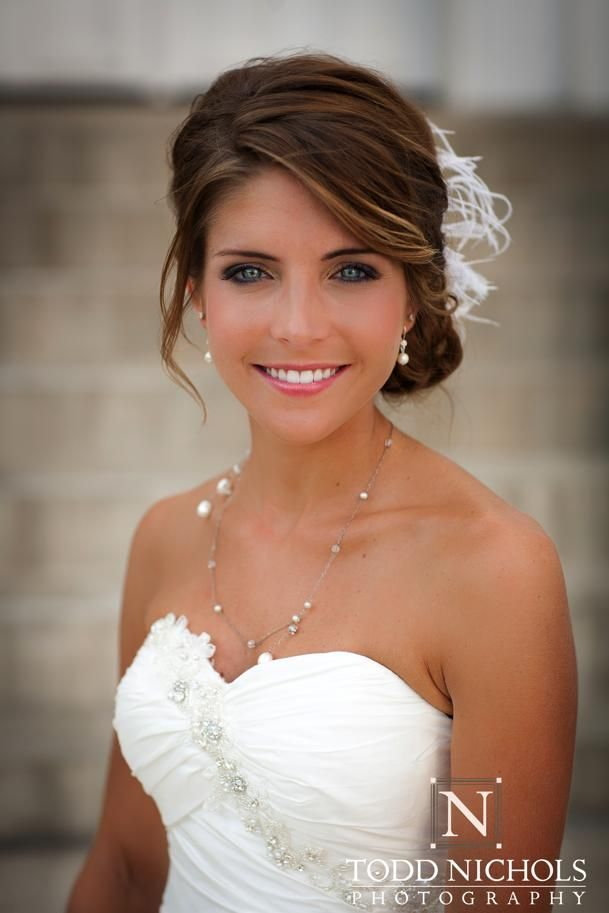 Pretty updo for your wedding, except without the feather thingy. Her dress is pretty too.
