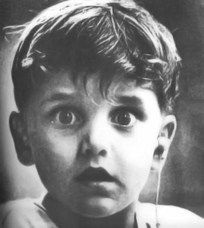 The face of a boy hearing sounds for the first time. This photo was taken by photographer Jack Bradley and depicts the exact moment this boy, Harold Whittles, hears for the very first time ever. The doctor 'otorhinologist' treating him has just placed an earpiece in his left ear.