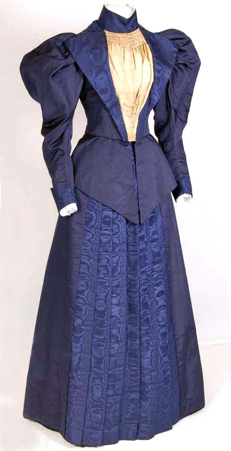 Two-pieced dress, possibly British, ca. 1895-1900, in dark blue silk rep. Bodice with high collar, leg o' mutton sleeves, wide lapels of blue moiré and inset of beige silk twill. Comes to a point front and back, lined with cotton, and closes with hooks & eyes. Raised skirt with pocket in right seam. Belt in dark blue velvet. Mode Museum, Antwerp