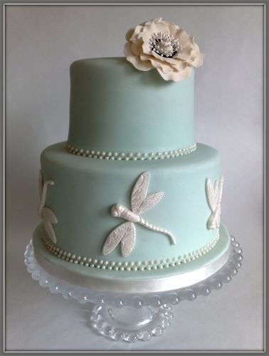 """Nicola""  : 2 Tier Cake in pale duck egg blue with ivory royal icing pearls.  Bottom tier is decorated with sugar paste dragonflies and top tier has an ivory bloom.    6"" & 8""   Price £265"