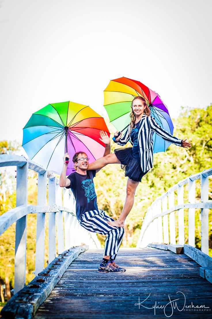 Engagement photo shoot for Switcharoo Circus. Rainbow umbrellas and Flag acrobalance  Photo credit to Kyle Wenham