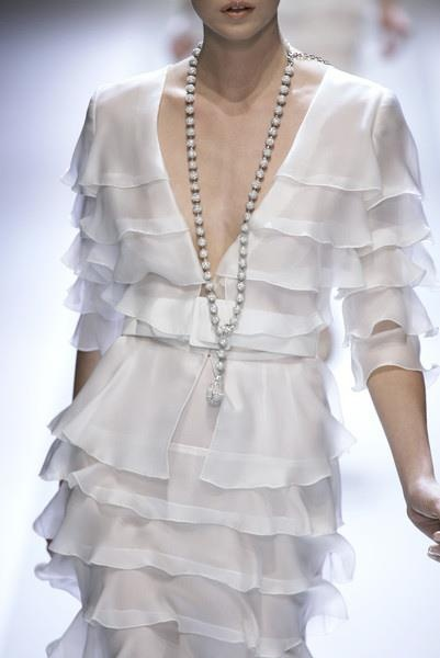 Silk chiffon midi with a deep v-neck bodice, white ruffled detail, a white cloth covered belt and long costume beaded necklace. Tres chic couture!