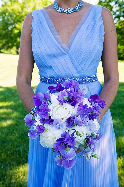 The blue-purple hue of this bridesmaid's gown is accented with a   bouquet of white peonies and purple sweet peas.