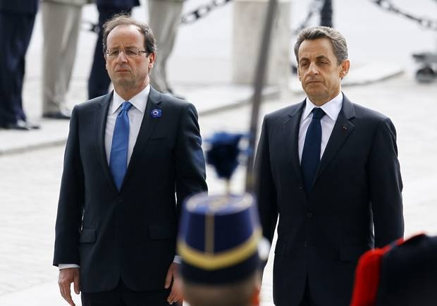 Outgoing French President Nicolas Sarkozy, right, and President-elect Francois Hollande observe a minute of silence at the Tomb of the Unknown Soldier during commemorations at the Arc de Triomphe in Paris, Tuesday May 8, 2012, marking the anniversary of the end of World War II in Europe. (AP Photo/Francois Mori, Pool)
