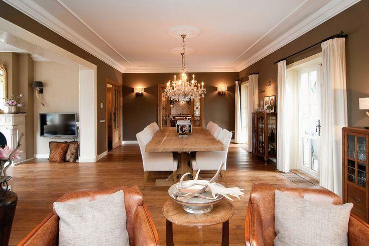 Interieur | MH Interieurdesign stijlvolle woonkamer lange eettafel met 8 stoelen, antieke kroonluchters, lederen fauteuils warme kleuren op de muren