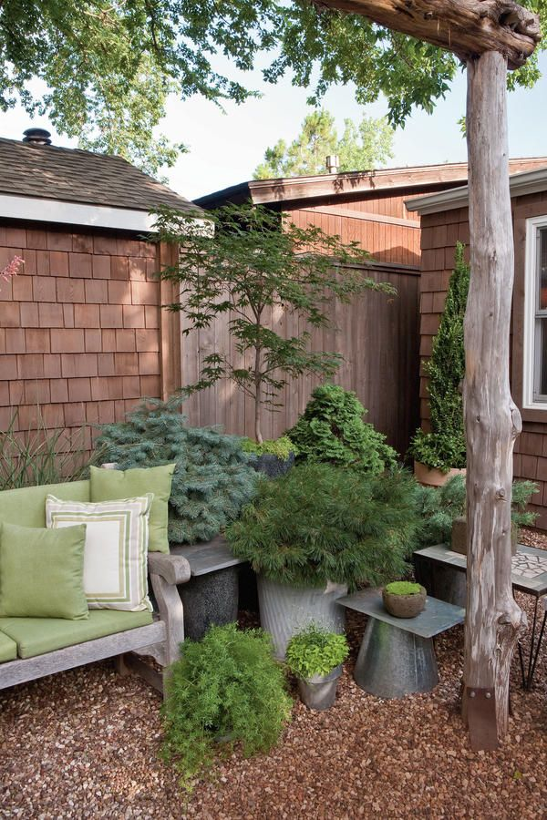 Use textural leaves for a more modern look. An assortment of plants in shades of green anchors this backyard corner and adds depth in the small space.