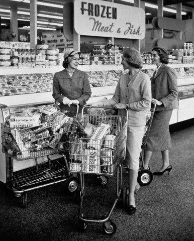 1950s three women pushing shopping carts meeting talking in frozen food aisle of supermarket.