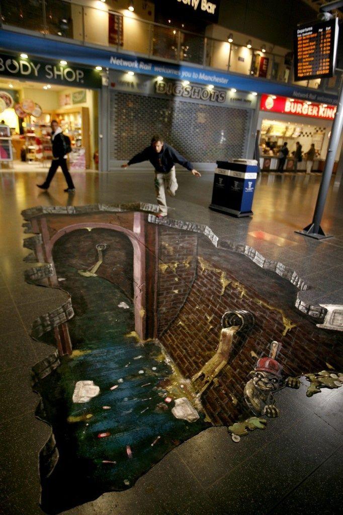 scary street art illusion: imagine falling into sidewalk sewage ; )
