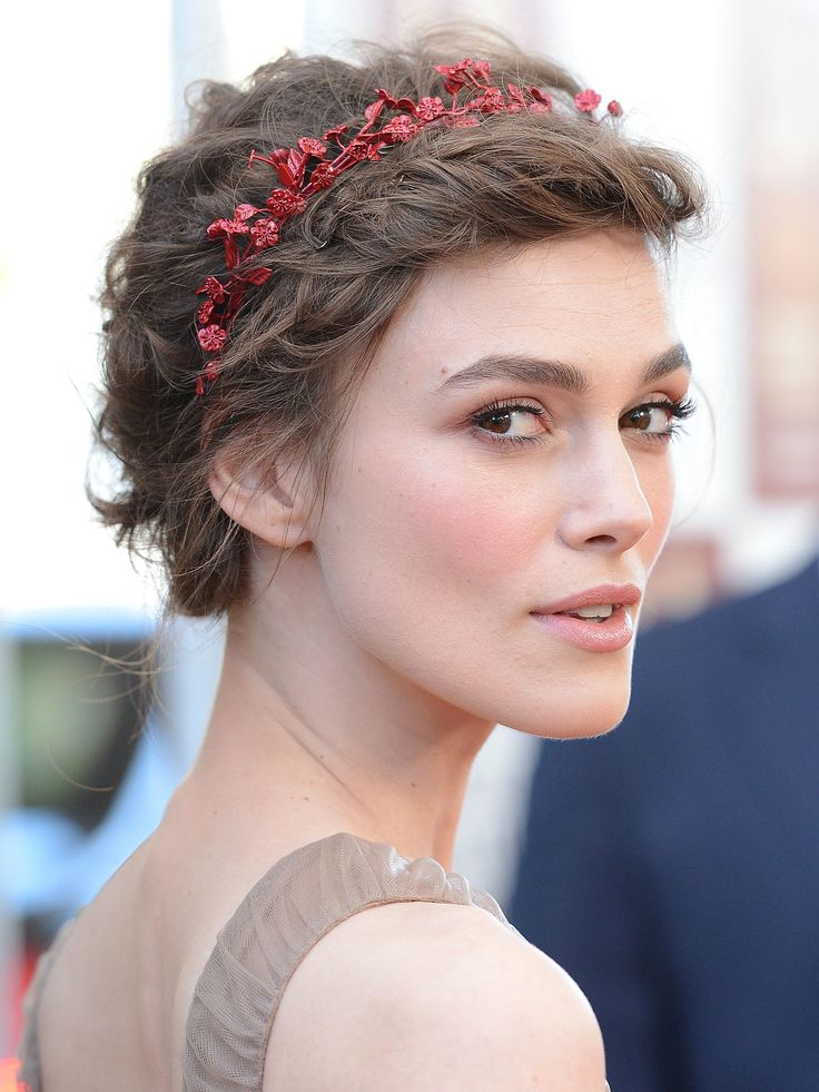 For Keira Knightley's angelic look, you'll need to curl your hair first using small rollers or a curling iron for tight, small curls. Then, run some hair oil or serum through for definition. Sweep all the hair off the face gently, and pin at the back of the head in a bun if it's long, or just curl by curl if it's shorter. Add a hair band in a contrasting color to finish and to keep the shorter front layers off your face.