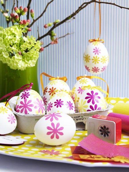 Mit kleinen, ausgestanzten Blüten lassen sich beim Osterbasteln mit Kindern ebenfalls tolle Kunstwerke gestalten. Pink und Gelb verleihen den Eiern hier eine enorme Leuchtkraft.