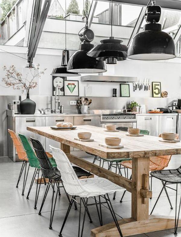 Verschillende #zwarte #hanglampen boven een #stoere #houten #eettafel in een #moderne #keuken. #different #pendant #lights #black #modern #kitchen
