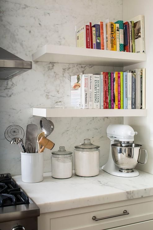 Fabulous kitchen features a stacked white floating cookbook shelves suspended over a white KitchenAid Mixer.