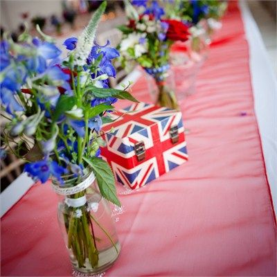 Pretty much everything at Sean and Rebekah's wedding adhered to their red, white and blue colour scheme. The bride even had a Union Jack patterned underskirt!The white tables were covered with red table runners, and jam jars filled with hand tied bunches of red, white and blue flowers were dotted around. Blue and white paper lanterns hung from the ceiling in the marquee, and a Union Jack screen covered a wall. Union Jack deck chairs were also dotted around for guests who fancied taking it…