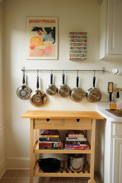 How to live in a small space: Accessorize your kitchen. Hang pots and pans from hooks or pot racks. Cute.