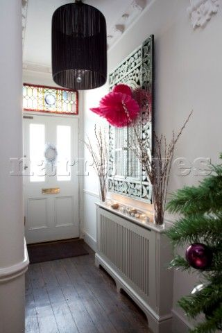 Decorative mirror above radiator in contemporary hallway of London home  UK