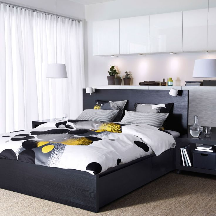 A Bedroom With A Black Brown MALM Bed, BESTÅ Storage With White Doors And  BOLLTISTEL