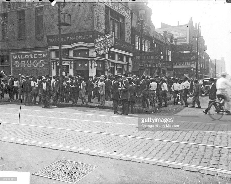 Image of a crowd of African American men standing on the sidewalks in front of a Walgreen Drugs at 3501 South State Street at the corner of 35th and South State Street in the Douglas community area of Chicago, Illinois, during a race riot, July or August 1919. Police officers are standing at the forefront of the crowd. From the Chicago Daily News collection. (Photo by Chicago History Museum/Getty Images)