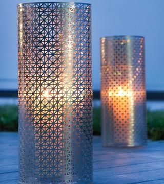 DIY Oversized Patio Lanterns.  Wrap a vase with aluminum radiator cover panel.  Secure with nuts & bolts.
