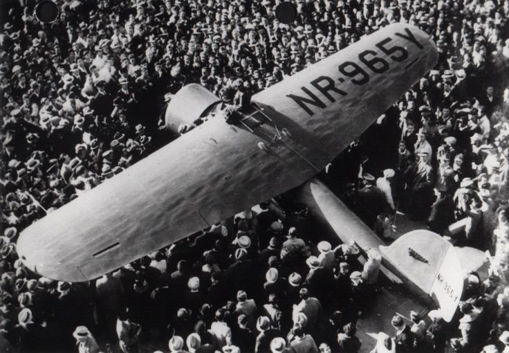 Amelia Earhart stands in the cockpit of her Lockheed Vega 5C (NR-965Y) surrounded by a large crowd after completing her nonstop solo flight from Hawaii to Oakland, California, January 11-12, 1935. | Source: National Air and Space Museum Archives