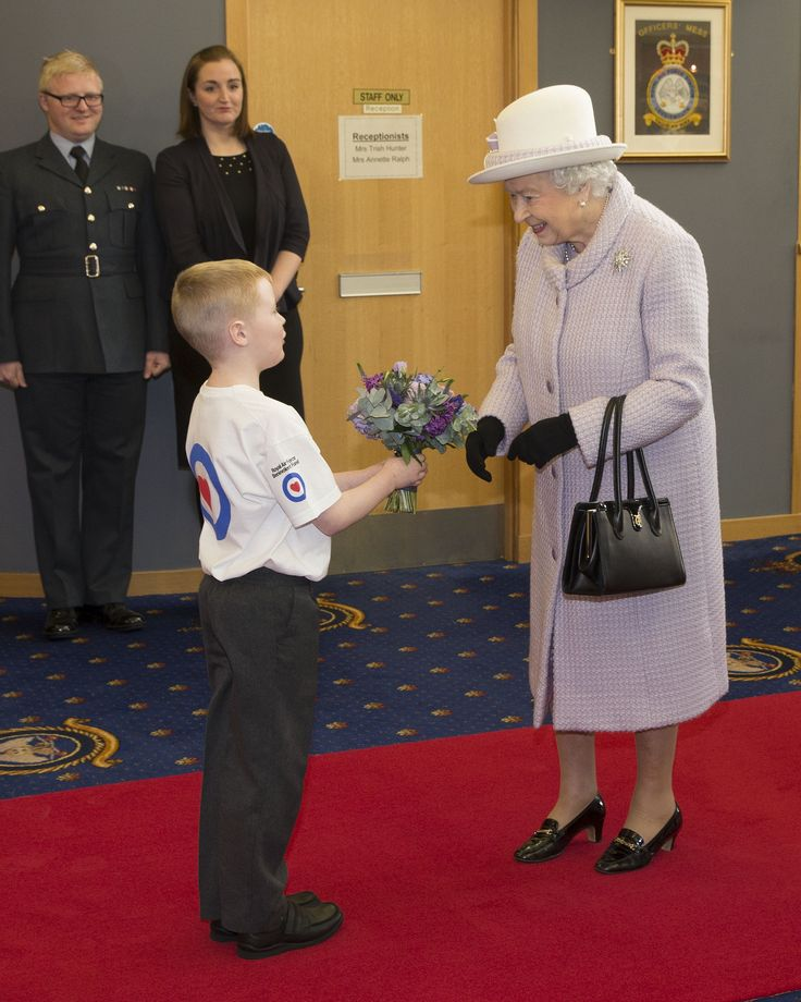 Her Majesty The Queen is presented with flowers from eight-year-old Lennon Gallagher