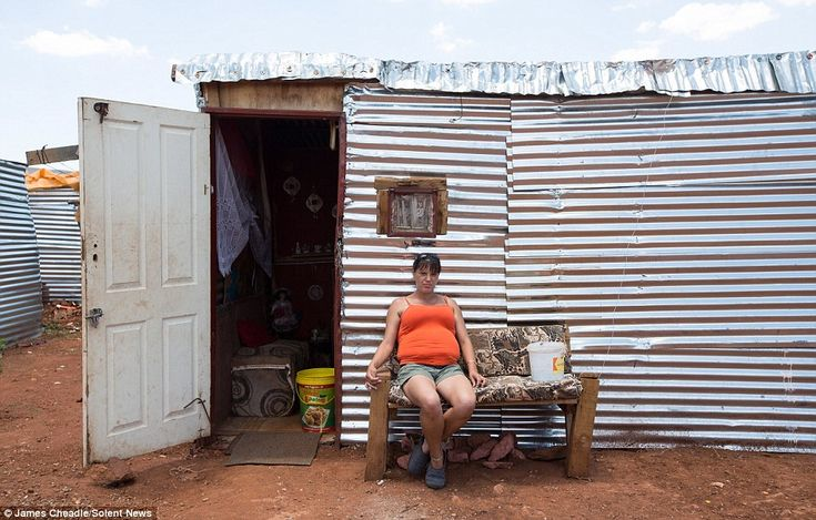 A woman sits outside her makeshift home in the squatter camp inMunsieville, a township  in the Krugersdorp area in Gauteng Province