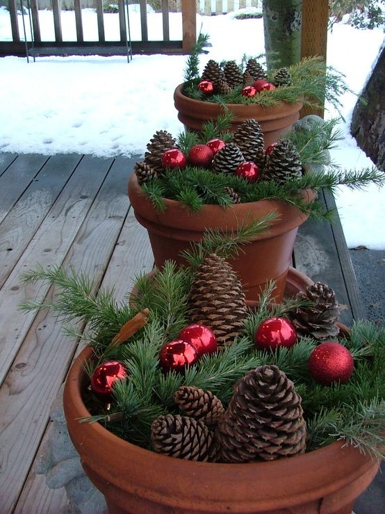 Natural and easy Christmas outdoor decor: faux terra cotta pots filled with evergreen branches, pine cones, and red ornaments for a pop of color!