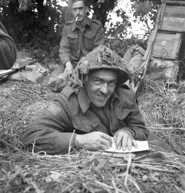 An unidentified infantryman of the 9th Canadian Infantry Brigade writing a letter home from the Normandy beachhead, France, ca. 8-9 June 1944. Photographer: Frank L. Dubervill