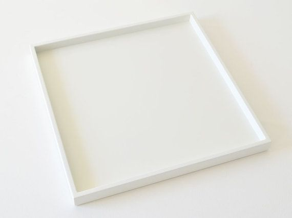 Bring a stylish accent to your ottoman or coffee table with a large square low profile white decorative tray. The smooth matte or gloss finish is the perfect complement to a variety of decor tastes.  • Available in two top-coat rated durable lacquered finishes - lustrous matte or sleek gloss for a polished look. • Handcrafted in the USA with professional premium materials for quality craftsmanship. • Youll appreciate the details - the softened edges to the smooth brush-free finish, the felt…