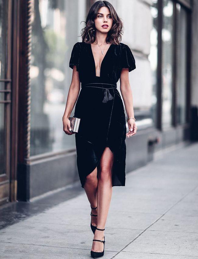 Robe noire avec décolleté plongeant et fendue à la jambe, ceinture à la taille, chaussures à talon noires,