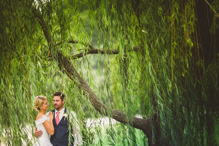 A bride and groom stand in the willows at Carrigan Farms. #NC #wedding
