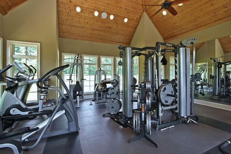 Home gym with plenty of windows, top-of-the-line equipment and vaulted ceiling with ceiling fan.