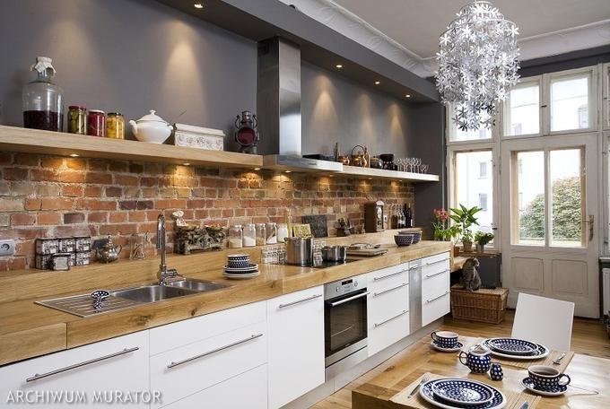 Naturalna cegła w kuchni, białe szafki i drewno